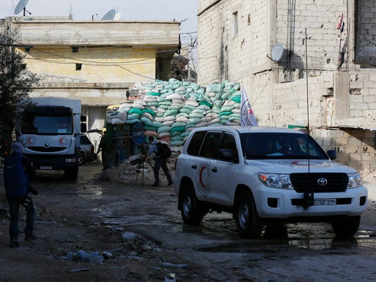 Trucks from the Syrian Arab Red Crescent carry medical