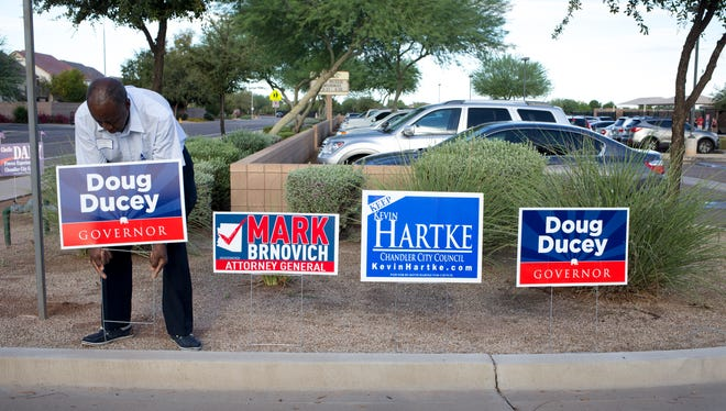 Polling Inspector Willie Rhodes moves signs to the edge of school property, August 26, 2014, at Hull Elementary School, 2424 E Maren Drive, Chandler. The polls opened at 6 a.m. and will close at 7 p.m., anyone in line at 7 p.m. will be allowed to vote.