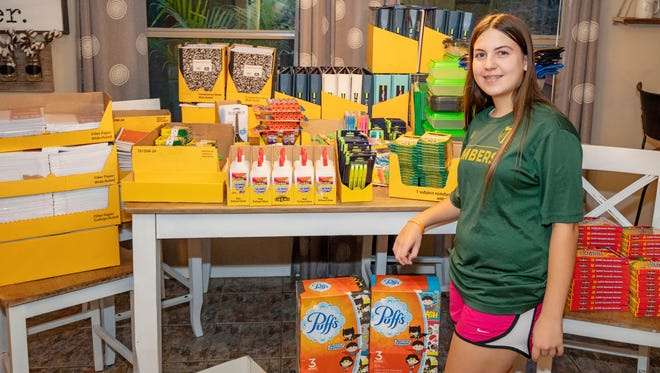 Lilianna Ortiz, 13, founder of Anna Packs, stands in front of school supplies donated by the community.