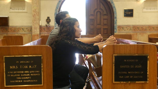 Fabiola Alvarez, front, and Allex Luna pray upon entering Our Lady of Solitude Church in Palm Springs. The two will be traveling to see Pope Francis during his visit to the United States.