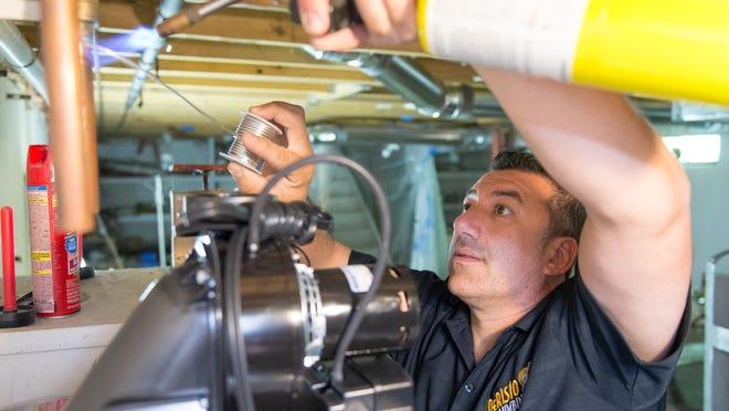 Plumber John DiTullio works on installing a hot water heater.