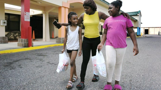Tiffany Jackson walks with daughter (right) Aszia Jackson, 10 and neighbor Shn'niyah Trotter, 9 after they picked up grab-and-go lunches and snacks at George Washington Carver Elementary School in Jacksonville Tuesday where the two girls go to school.