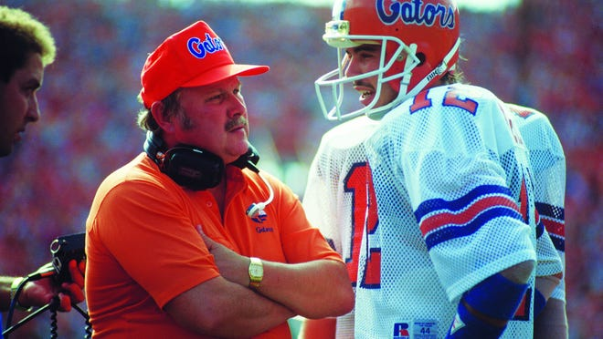Florida head football coach Galen Hall, left, talks to QB Kerwin Bell on the sideline in 1985.