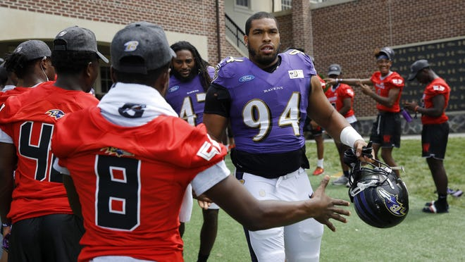 Defensive tackle Carl Davis, right, then with the Baltimore Ravens, greets fans as he walks to a joint training camp practice with the Los Angeles Rams in August 2018 at the Ravens' headquarters in Owings Mills, Md.
