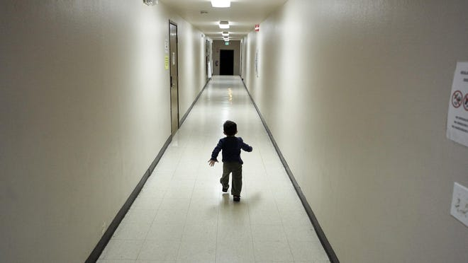 """An asylum-seeking boy from Central America is shown in 2018 running down a hallway at a San Diego shelter after arriving from an immigration detention center. Agencies working to reunite families separated by Trump's """"zero tolerance"""" policy said this week they still can't find the parents of 545 kids."""