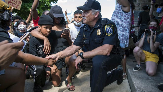Ypsilanti Police Chief Tony DeGiusti shakes hands with a protestor while taking a knee with demonstrators in a moment of solidarity during a police brutality protest in downtown Ypsilanti on Saturday, June 6, 2020.