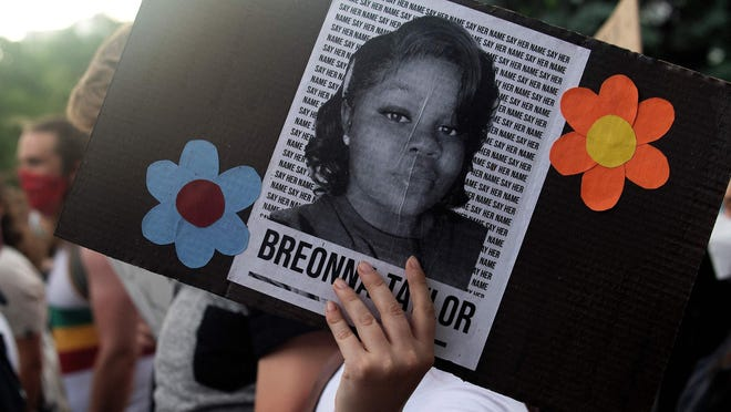 A demonstrator holds a sign with the image of Breonna Taylor, a black woman who was fatally shot by Louisville Metro Police Department officers, during a protest against the death George Floyd in Minneapolis, in Denver, Colo., on June 3, 2020.