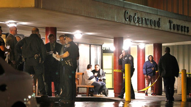 Rochester police huddle outside the lobby of Cedarwood Towers to investigate a homicide Wednesday evening.