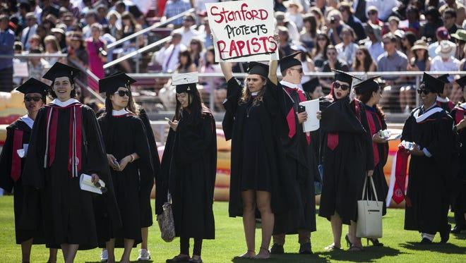 Graduating student Andrea Lorei, who helped organize campus demonstrations at Stanford, holds a sign in protest during the 'Wacky Walk' before the school's 125th commencement ceremony on June 12, 2016.