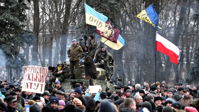 People attend a rally outside the parliament in Kiev on Feb. 27, 2014. Deposed Ukrainian president Viktor Yanukovych the same day said he still considers himself to be Ukraine's head of state but asked Russia to ensure his personal security.