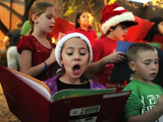 Children enjoy singing at the tree lighting ceremony at the Civic Center and along the parade route.