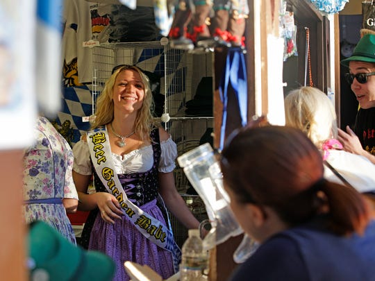 Sigrid Degner, Germantown, laughs inside a booth selling merchandise at Oktoberfest in 2014. The event has been hosted on the grounds near the Bavarian Bierhaus for over 60 years and this year is no different.