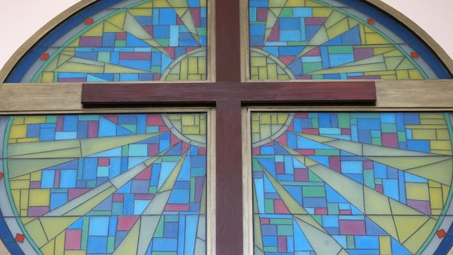 A cross and stained glass decoration hangs on the wall at Wildwood Church.