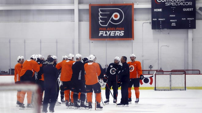 Flyers players gather around head coach Alain Vigneault during training camp at the Skate Zone.