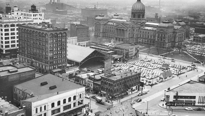 This view of Downtown Indianapolis looking southwest toward the Statehouse, taken March 18, 1953, shows the arched-roof Traction Terminal Station in center. The station was dismantled in 1968 and taken to the Indiana Transportation Museum at Forest Park in Noblesville. Three years after this photo was taken, the Traction Terminal Building (to the left of the terminal), was bought by Blue Cross and Blue Shield and renamed the Blue Cross and Blue Shield Building. It was razed in 1972 to make way for a new Blue Cross building. This view was taken from the roof of the Indiana Bell Telephone Co. Building and shows the intersection of Illinois and Ohio streets in the foreground.