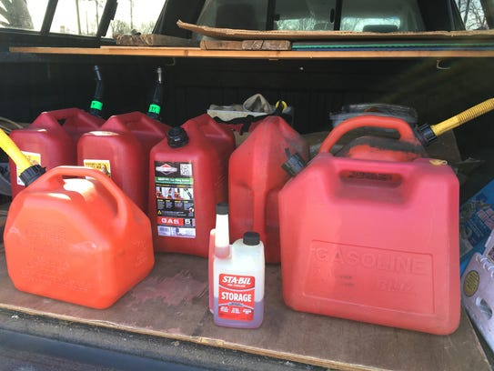 John Raymond puts gas cans in his truck on days when