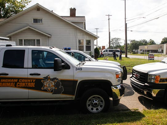 Ingham County Animal Control officers work at a house