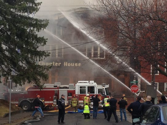 Firefighters work at the scene of the fire at the Chapter