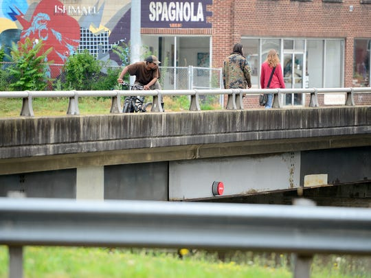 Terry Marzelle rides his bicycle across the Haywood Road bridge over I-240 in West Asheville  on June 22. Marzelle was later arrested by police, who supporters say mistreated him.