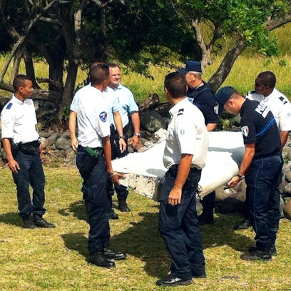 Police and gendarmes carry a piece of debris from an