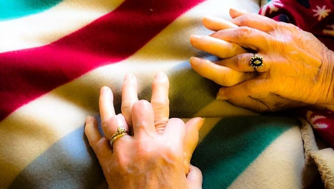 During her first stay at a nursing home, Helen holds hands with her daughters.