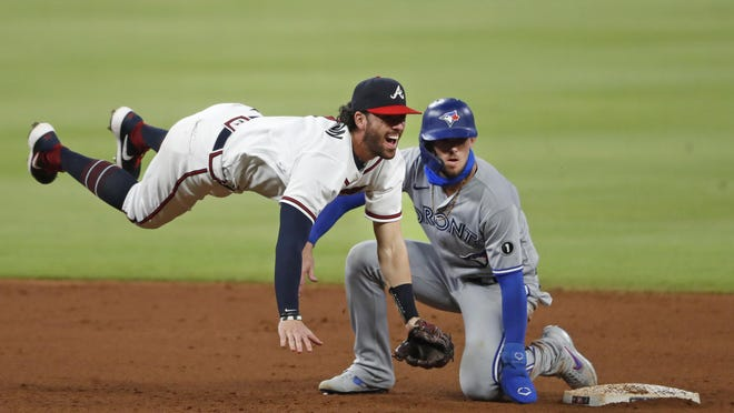 Braves shortstop Dansby Swanson (7) avoids the Toronto Blue Jays' Cavan Biggio (8) as he turns a double play on a Teoscar Hernandez ground ball in the sixth inning of a  game Tuesday night in Atlanta.