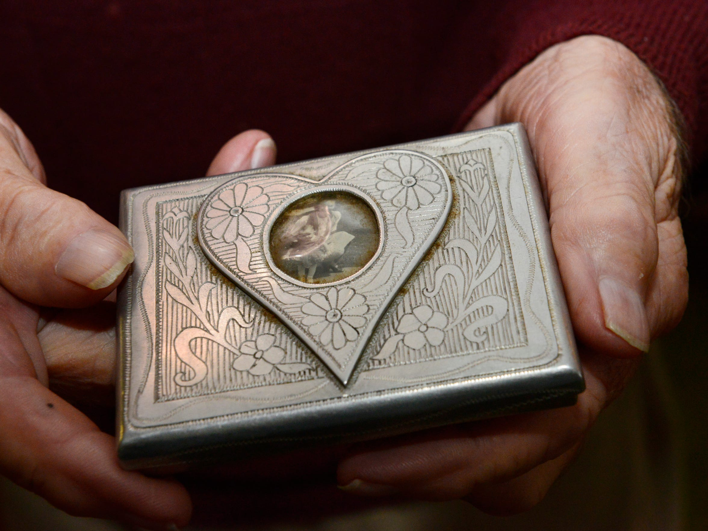 A Russian prisoner made Charles Holcomb this cigarette case from aircraft aluminum in exchange for food. Earlier, the photo of his future wife of 70 years and niece was confiscated inside a matchbook by an interrogator, who returned only the photo.