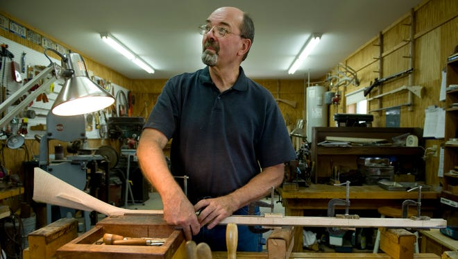 Marvin J. Kemper of Wadesville, Ind., takes a peek at the musical artist playing in his shop, Liberty Longrifles, while working on a Kentucky longrifle Tuesday afternoon. Kemper built his first rifle in 1972 when he was 13 years old.