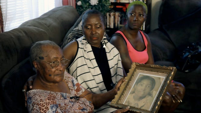 In this Aug. 23, 2017 photo, Ruby Williams, from left, holds a photo of her daughter Brenda, as she sits with her other daughters Sharon Scott and Sheila Williams in Tampa. After decades of waiting to know what happened to their relative, Tampa Police officials told the family that they found a DNA match in a jawbone found in 1986. Brenda Williams, a young mother of two, went missing in 1978.