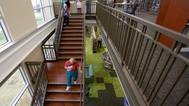 People traverse the stairway to the second floor of the Everett Roehl Marshfield Public Library, which had a soft opening Tuesday morning, September 6, 2016.