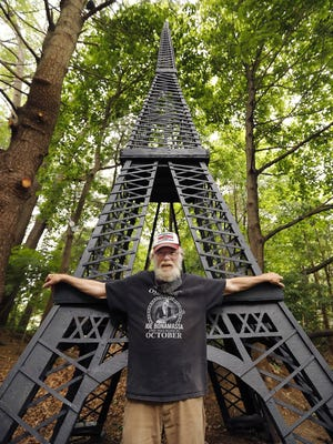 Steve Temple  with the wooden replica  of the Eiffel Tower that he built.