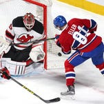 Devils goalie Cory Schneider makes a save against Canadiens center Lars Eller.