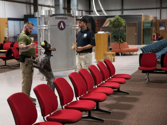 Nick VonCanon, left, of the, Federal Protective Service, with Beni, a German short-haired pointer, discusses training to find explosives with Transportation Security Administration with training instructor Shawn Farrens, inside the replica of an airport terminal at the National Canine Training Center in San Antonio on Sept. 13, 2017.