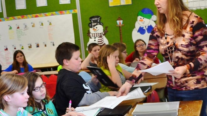 Gillett Elementary teacher Nicole Soper hands out an informational sheet to students in her 5th Grade class in March 2016.