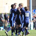 Nick Steed, left, congratulates Alec Cutler after Cutler scored a goal Sunday in Elmira Notre Dame's 9-1 victory over Solomon Schechter in the Class C boys soccer state championship game at Middletown High School.