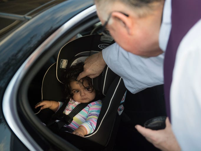 Father Noel McGrath marks Priscilla Ajami, 9 months,