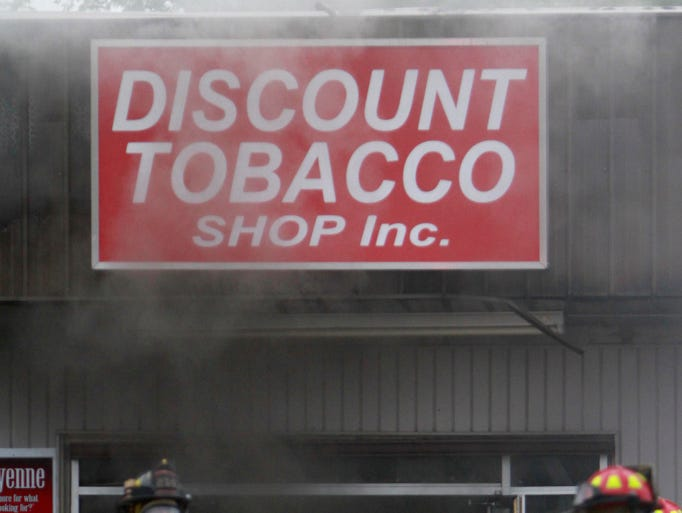 Smoke pours from Discount Tobacco Shop Inc. building as firefighters work to extinguish a fire in the building on Tuesday, May 13, 2014.
