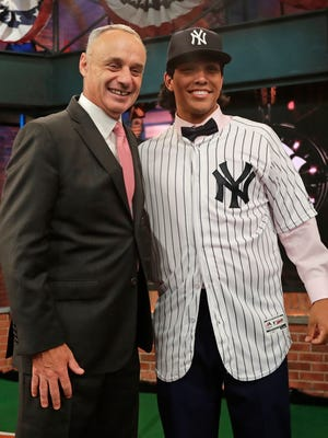 Anthony Seigler, right, a catcher from Cartersville High School in Georgia, poses for photos with Baseball commissioner Rob Manfred after being selected 23rd by the New York Yankees during the first round of the Major League Baseball draft Monday, June 4, 2018, in Secaucus, N.J.