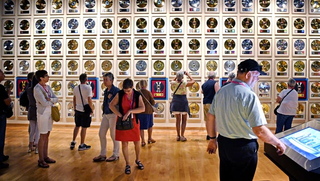 Visitors check out the wall of gold records at the Country Music Hall of Fame and Museum. The museum is free on Dec. 16.