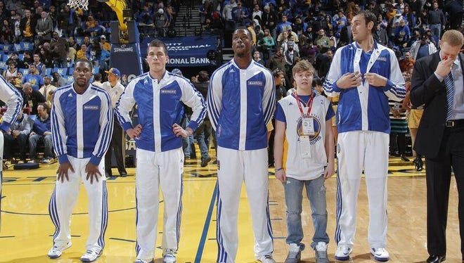 Saydel student Cole Vitiritto stands next to Harrison Barnes during the pregame huddle of a Golden State Warriors game during his Make-A-Wish trip to San Francisco.