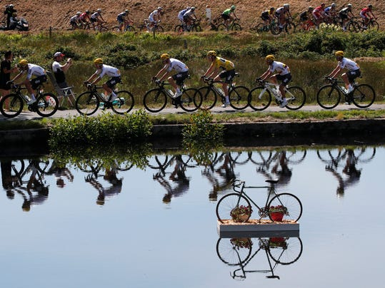 FILE - In this Wednesday, July 5, 2017 file photo Britain's Geraint Thomas, wearing the overall leader's yellow jersey, and new overall leader Britain's Chris Froome, left of Thomas, are reflected in a pond as they ride in the pack during the fifth stage of the Tour de France cycling race over 160.5 kilometers (99.7 miles) with start in Vittel and finish in La Planche des Belles Filles, France. (AP Photo/Christophe Ena, File)