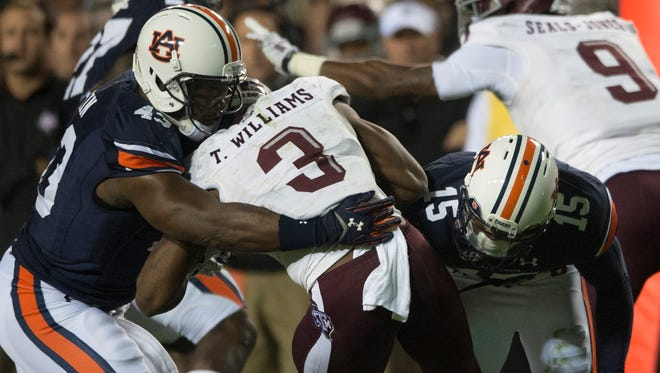 Auburn linebacker Anthony Swain and defensive back Joshua Holsey (15) tackle Texas A&M running back Trey Williams (3) during the NCAA football game between Auburn and Texas A&M on Saturday, Nov. 8, 2014, in Auburn, Ala. Texas A&M defeated Auburn 41-28 after Auburn fumbled twice on there last two drives.