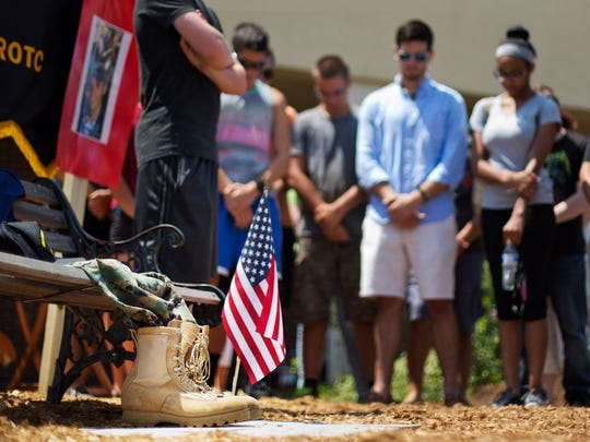 Boot sits next to an American flag Friday as current and former JROTC students hold a moment of prayer at a memorial for  victim Skip Wells at his former school, Sprayberry High School, in Marietta, Ga. Memorials  also were held in Chattanooga for the four Marines killed in Thursday's shooting in Chattanooga.