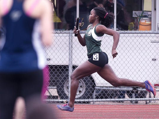 Rice's Sonia John charges to the finish as the winning leg of the Green Knights' 4x100-meter relay squad at the Burlington Invitational track meet on Saturday at D.G. Weaver Athletic Complex. John and Rice set a Division II record.