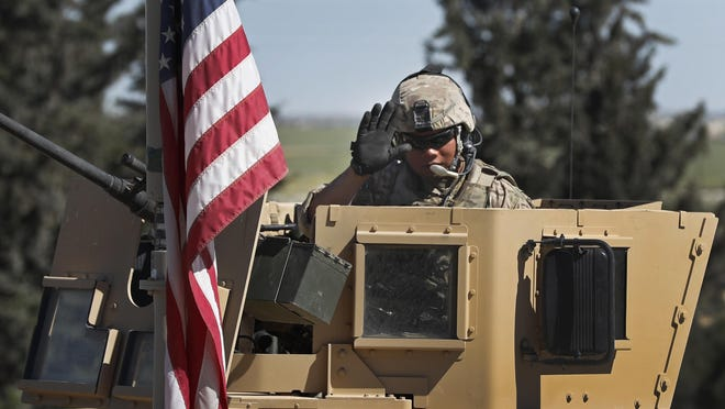 In this April 4, 2018 photo, a U.S. soldier waves as he sits on an armored vehicle, at a road leading to the tense front line with Turkish-backed fighters, in Manbij town, north Syria. President Donald Trump's decision to withdraw troops from Syria has rattled Washington's Kurdish allies, who are its most reliable partner in Syria and among the most effective ground forces battling the Islamic State group. Kurds in northern Syria said commanders and fighters met into the night, discussing their response to the surprise announcement Wednesday, Dec. 20, 2018. (AP Photo/Hussein Malla)