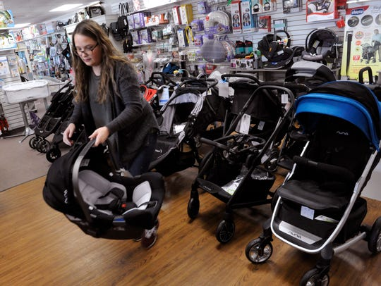 Elise Oler sorts strollers and baby carriers Wednesday at Little Giant Kidz. Saturday is Small Business Saturday, where shoppers are encouraged to patronize local stores.