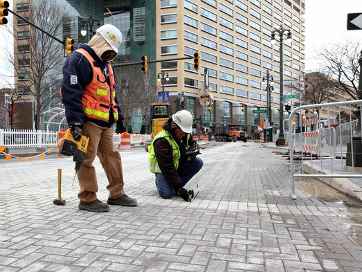 M-1 Rail workers mark the bricks on the streets as