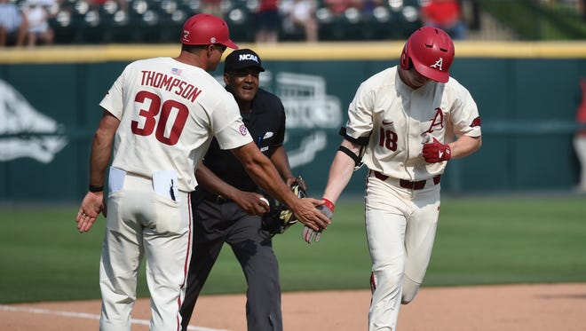 Arkansas' Heston Kjerstad (right)celebrates with thirdbase coach Nate Thompson after hitting a long home run against Oral Roberts in the opening game of the NCAA's Fayetteville Regional on Friday afternoon.