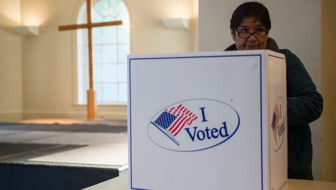 A woman cast her ballot at a church polling station in Fairfax, Virginia during the US presidential election on November 8, 2016.  / AFP / Andrew CABALLERO-REYNOLDS        (Photo credit should read ANDREW CABALLERO-REYNOLDS/AFP/Getty Images)