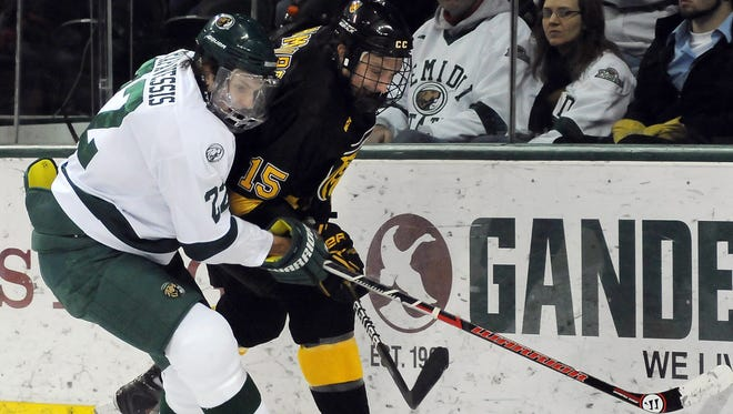 Colorado College's Andrew Hamburg, right, and Bemidji State's Matt Prapavessis, left, chase after a puck during the first period of a college hockey game Saturday, Feb. 11, 2012 in Bemidji, Minnesota.